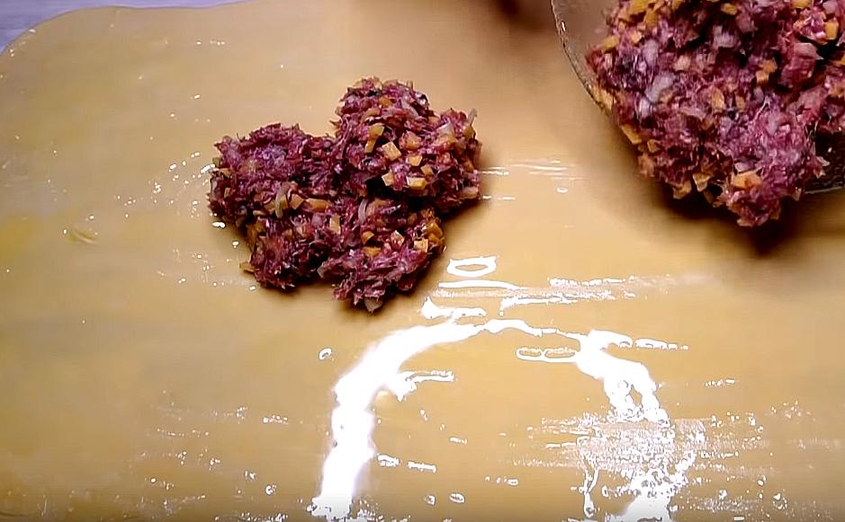 Остатки масла кладем в начинку, которую равномерно раскладываем по поверхности теста