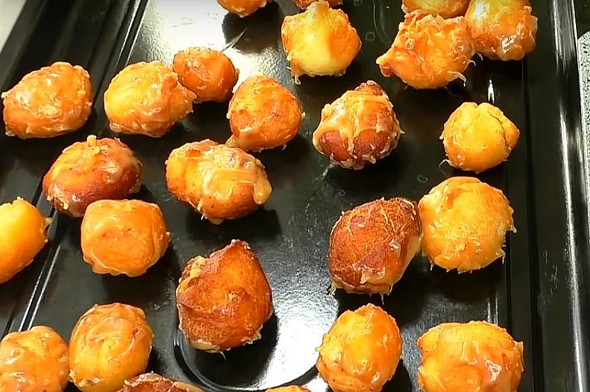 Карамель не должна остыть. Горячей массой заливаем пончики, не снимая их с противня, размешиваем, чтобы глазурь распределилась по ним