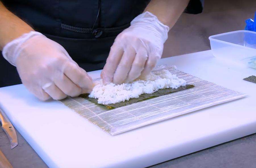 Выкладываем на лист нори (лежащем на коврике) рис. С одной стороны – чтобы на 1 см не выступал за нори, с другой – чтобы на 1 см выступал за нори
